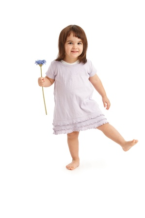 Cute little girl with flower in spring dress, standing on one foot. photo