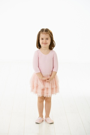 standing alone: Full length portrait of cute little girl (4-5 years) wearing ballet costume looking at camera, smiling. Studio shot over white background. Stock Photo