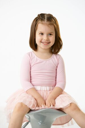 Portrait of happy little girl wearing ballet costume sitting on high chair against white background, smiling. photo