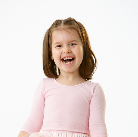age 5: Portrait of laughing little girl in pink dress over white background.