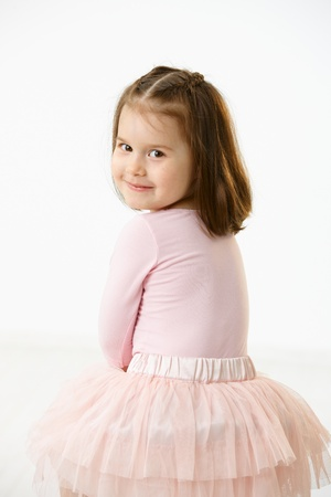 age 5: Portrait of happy little girl (4-5 years) wearing ballet costume looking back at camera, smiling. Studio shot over white background. Stock Photo