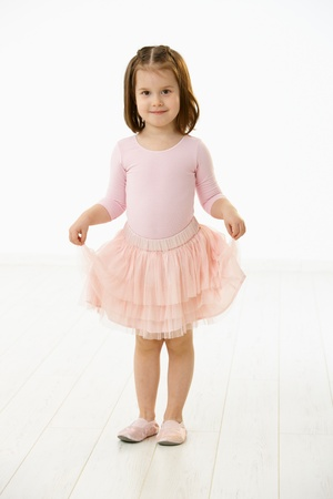 Full length portrait of cute little girl (4-5 years) wearing ballet costume looking at camera, smiling. Studio shot over white background. Stock Photo - 8747732
