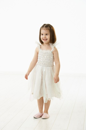 Portrait of happy little girl (4-5 years) wearing ballet costume, smiling. Studio shot over white background. photo