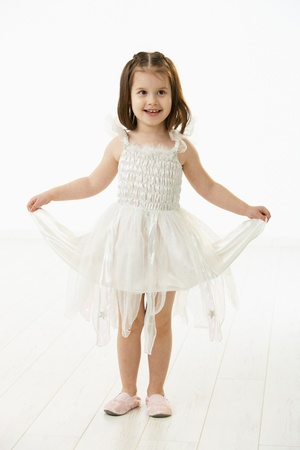 Full length portrait of cute little girl (4-5 years) wearing ballet costume, smiling. Studio shot over white background. photo