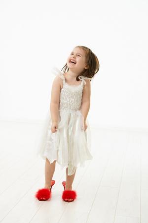 Petite fille essayant de marcher dans les mères big shoes, en riant. Studio abattu sur fond blanc.