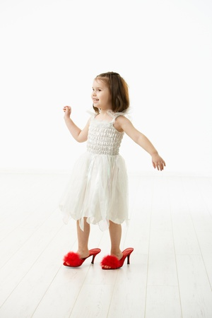 big five: Little daughter trying to walk in mothers big shoes, laughing. Studio shot over white background. Stock Photo