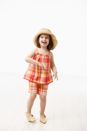 big five: Piccola figlia cercando le madri grandi scarpe, sorridente. Studio girato su sfondo bianco.