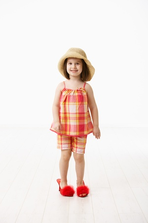 big five: Little daughter trying mothers big shoes, looking at camera, smiling. Studio shot over white background.