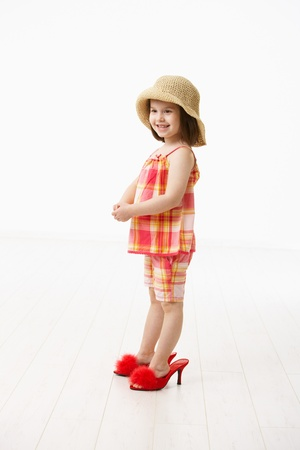 big shoes: Little daughter trying mothers big shoes, smiling. Studio shot over white background. Stock Photo