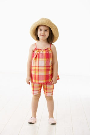 4 5: Portrait of cute little girl (4-5 years) wearing summer dress and straw. Studio shot over white background.