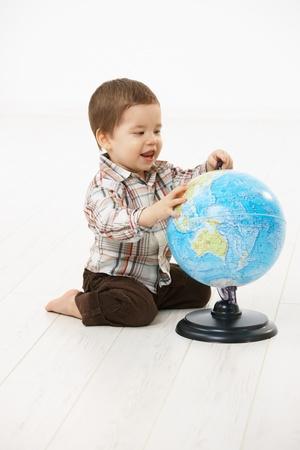 2 to 3 years: Carino piccolo bambino (2-3 anni) seduta sul pavimento, giocando con il globo su sfondo bianco.