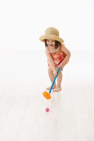 Little girl (4-5 years) in summer dress and straw playing golf indoor. White background. photo