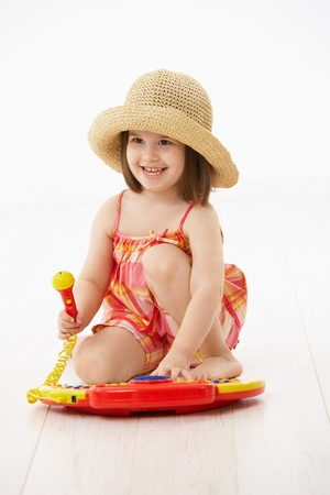 little girl sitting: Little girl sitting on floor playing with toy music instrument over white background. Stock Photo