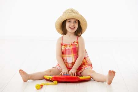 Little girl sitting on floor playing with toy music instrument over white background. photo