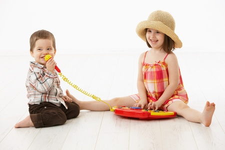 Happy kids playing on toy music instrument, little boy singing to microphone over white background. photo