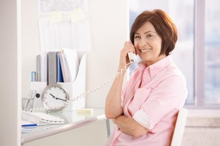 Portrait of senior professional sitting at office desk, using landline phone, smiling. photo
