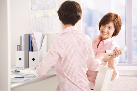 Young office worker woman handing over phone to senior female colleague. photo