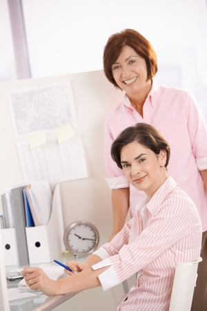Portrait of confident female office workers, smiling at camera together. photo