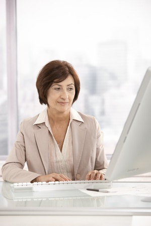 Senior businesswoman working on computer in office. photo