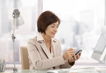 woman smartphone: Mature female executive using smartphone in office, smiling.