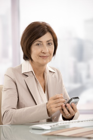 Portrait of smiling female businesswoman holding smartphone, looking at camera. photo