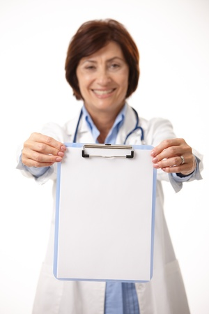 Smiling senior medical doctor holding clipboard in focus. photo
