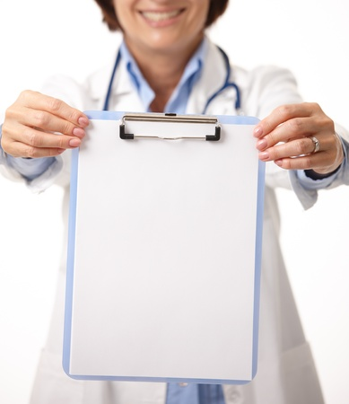held: Blank clipboard in focus, held by smiling doctor. Stock Photo