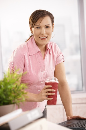 Businesswoman standing at desk holding coffee cup, looking at camera, smiling. photo