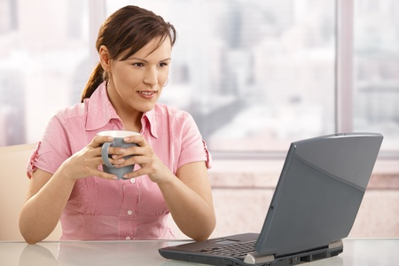 Businesswoman drinking coffee at desk, looking at laptop screen, smiling. photo