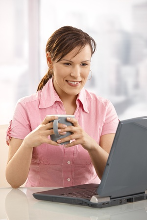 Office worker drinking tea at desk, looking at laptop screen, smiling. photo
