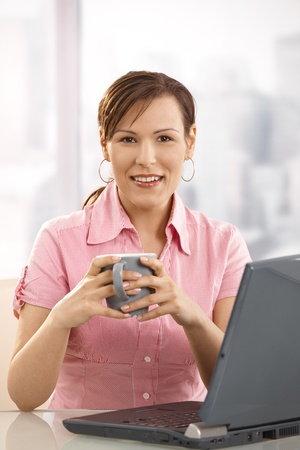 Young businesswoman drinking tea at desk, looking at camera, smiling. photo