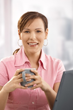 Happy businesswoman drinking coffee at desk, looking at camera, smiling. photo