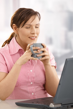 Young businesswoman enjoying her tea at desk with closed eyes. Stock Photo - 8748776