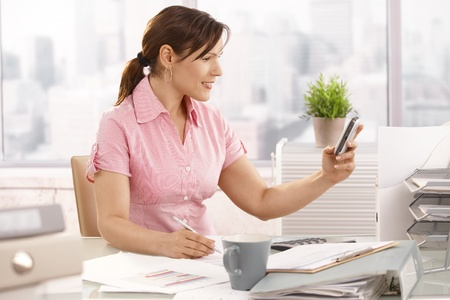 Casual office worker sitting at office using mobile phone, smiling. photo