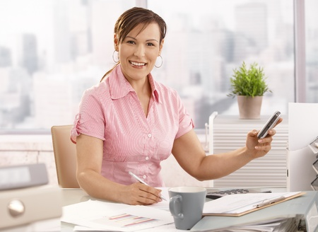 Young businesswoman sitting at office using mobile phone, smiling. photo