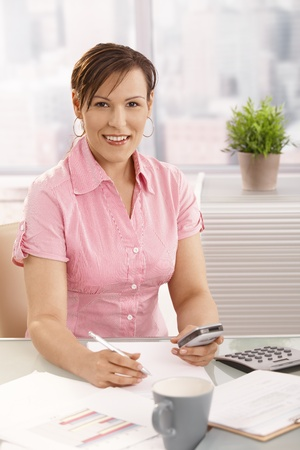 Young businesswoman working at desk using mobile phone, smiling. photo