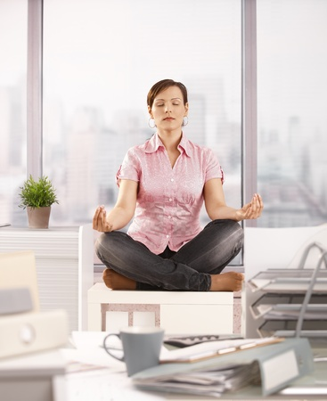 office cabinet: Office worker sitting in lotus posture on office cabinet, meditating.