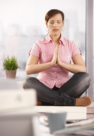 doing business: Portrait of relaxed office worker sitting on cabinet, doing yoga meditation with closed eyes, smiling.
