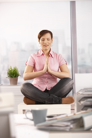 Office worker having a break, doing yoga meditation sitting in front of windows. photo