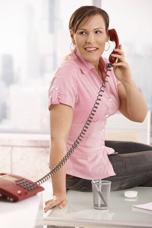 Casual office worker sitting on desk talking on phone, smiling. Stock Photo - 8748755
