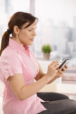 Casual office worker sitting on desk using smartphone, smiling. photo