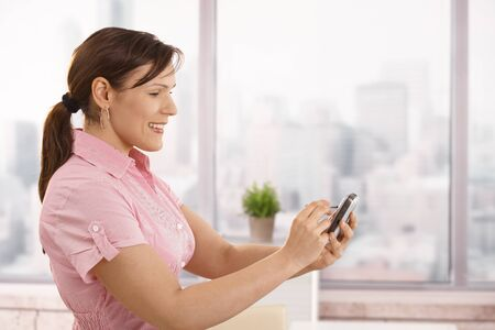 Portrait of young businesswoman using smartphone in office, smiling. photo