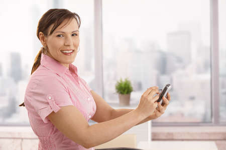 Portrait of young businesswoman using smartphone in office, looking at camera, smiling. photo