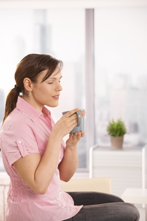 Office worker sitting on desk, enjoying her tea with closed eyes. photo