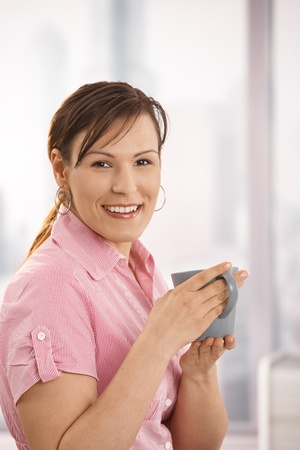 Portrait of happy office worker holding tea cup, looking at camera, smiling. photo