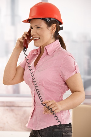 Portrait of young architect talking on landline phone in office, smiling. Stock Photo - 8748783