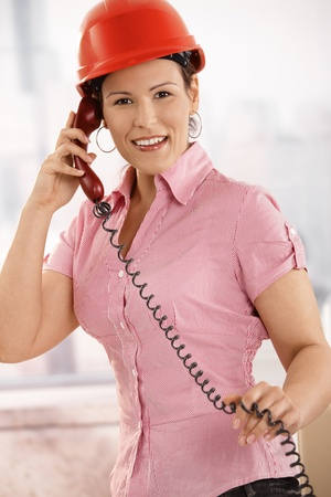 Portrait of female architect talking on landline phone in office, looking at camera, smiling. photo