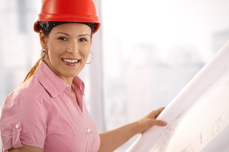 Portrait of female architect holding floor plan, looking at camera, smiling. photo