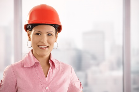 Portrait of young architect wearing red hardhat, looking at camera, smiling. photo