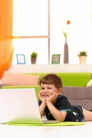 Happy little boy (5 years) lying on floor at home browsing internet on laptop computer, looking at camera, smiling. photo